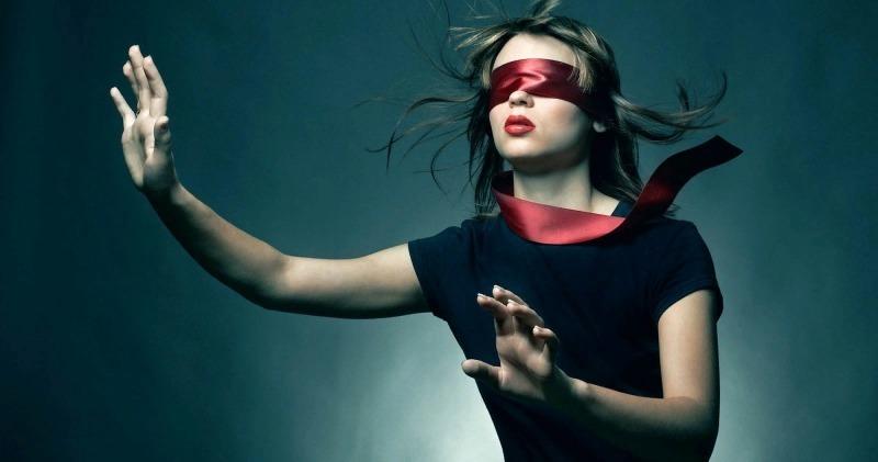 Девушка с красной повязкой на глазах двигается на ощупь